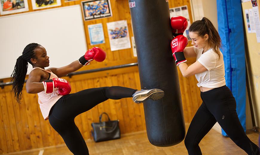Deux femmes s'entrainent à la boxe sur un sac de frappe