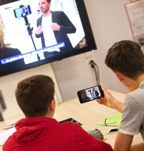 personnes étudiants dans un learning lab avec un téléphone et une télévision