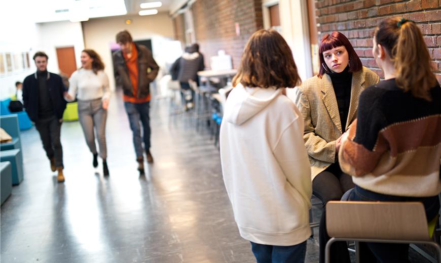 personnes qui discutent dans un des couloirs de l'Université